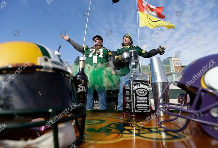 Scott Schwartz, left, and Justin Sipla read a poem in the parking lot at Lambeau Field before an NFL football game between the Green Bay Packers and the Minnesota Vikings, in Green Bay, Wis