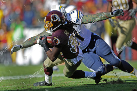 E.J. Biggers, Nick Hardwick. Washington Redskins cornerback E.J. Biggers is stopped by San Diego Chargers center Nick Hardwick after Biggers' intercepted a San Diego Chargers quarterback Philip Rivers pass during the first half of a NFL football game in Landover, Md