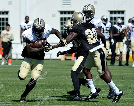 New Orleans Saints wide receiver Joseph Morgan (13) runs the ball around a couple of defenders during the team's NFL football training camp in White Sulphur Springs, W. Va