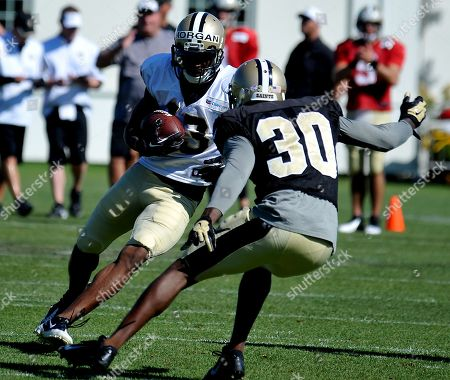New Orleans Saints wide receiver Joseph Morgan (13) tries to get around New Orleans Saints defensive back Kenny Phillips (30) during the team's NFL football training camp in White Sulphur Springs, W. Va