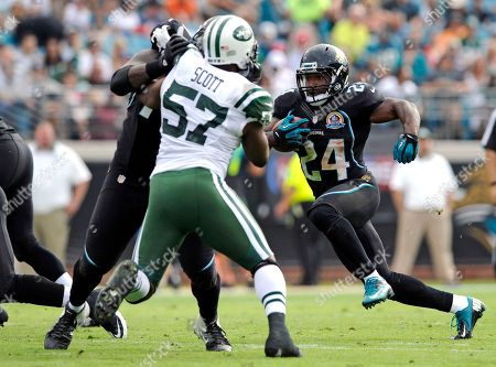 Montell Owens, Bart Scott. Jacksonville Jaguars fullback Montell Owens (24) runs for yardage as he gets a block from a teammate on New York Jets inside linebacker Bart Scott (57) during the first half of an NFL football game, in Jacksonville, Fla