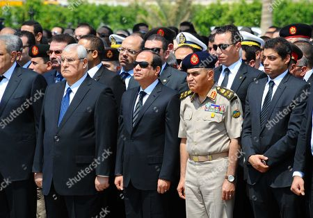 In this picture provided by the office of the Egyptian Presidency, Egyptian president Abdel-Fattah el-Sissi, center front, Minister of Defense Sedki Sobhi, center right and former acting Egyptian president Adly Mansour, second left, attend the military funeral of Hisham Barakat the top judicial official in charge of overseeing the prosecution of thousands of Islamists, including former President Mohammed Morsi in Cairo, Egypt, . Egyptian president Abdel-Fattah el-Sissi promised to speed up proceedings against extremists by amending laws and freeing up the judiciary, a day after the country's top prosecutor was killed in a car bombing