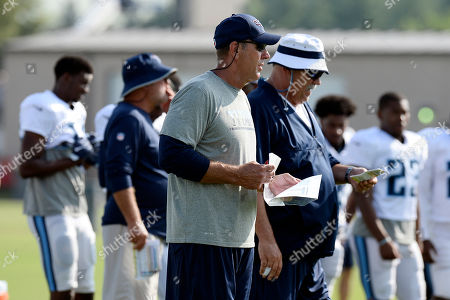 Stock Image of Mike Mularkey, Russ Grimm. Tennessee Titans head coach Mike Mularkey, third from left, and offensive line coach Russ Grimm watch during NFL football training camp, in Nashville, Tenn