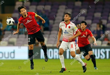 Japan's Urawa Reds Yuki Abe, left, heads the ball chased by Morocco's Wydad Athletic Club Walid El Karti during the Club World Cup soccer match for the fifth place between Wydad Athletic Club and Urawa Reds at the Hazza Bin Zayed stadium in Al Ain, United Arab Emirates