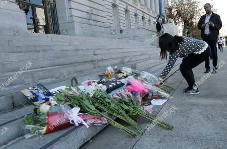 Ruby Chen leaves flowers for Mayor Ed Lee on the steps of City Hall in San Francisco, . Lee, who oversaw a technology-driven economic boom in San Francisco that brought with it sky-high housing prices despite his commitment to economic equality, died suddenly early Tuesday at age 65