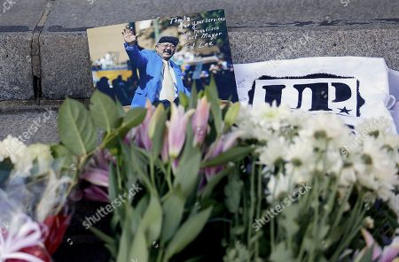 A photo of Mayor Ed Lee is shown with flowers on the steps of City Hall in San Francisco, . Lee, who oversaw a technology-driven economic boom in San Francisco that brought with it sky-high housing prices despite his commitment to economic equality, died suddenly early Tuesday at age 65