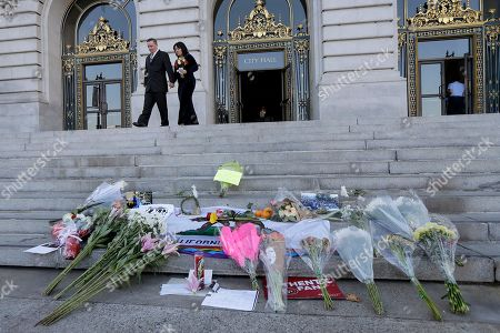 Newlyweds Gary Thomas and Mary Wong-Thomas walk behind flowers and signs left for Mayor Ed Lee on the steps of City Hall in San Francisco, . Lee, who oversaw a technology-driven economic boom in San Francisco that brought with it sky-high housing prices despite his commitment to economic equality, died suddenly early Tuesday at age 65