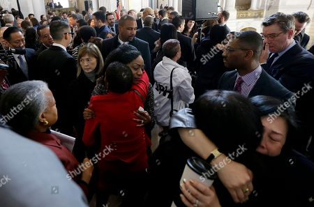 Supervisor Malia Cohen, center facing, hugs supporters after a news conference at City Hall in San Francisco, . Mayor Ed Lee, who oversaw a technology-driven economic boom in San Francisco that brought with it sky-high housing prices despite his commitment to economic equality, died suddenly early Tuesday at age 65