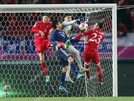 Japan's goalie Kosuke Nakamura (C) punches the ball