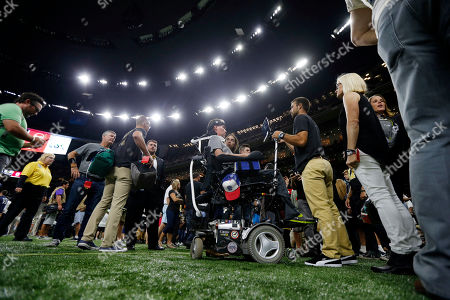 Former New Orleans Saints player Steve Gleason sits on the sideline before an NFL football game between the New Orleans Saints and the Atlanta Falcons in New Orleans
