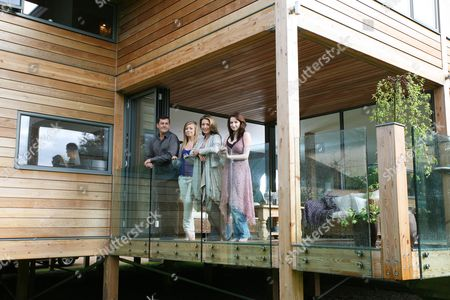 Julia Kendell and her fiance Andrew Hughes-Hallett with daughters Maddy (18) and 15-year-old Sophie (blue top) on the open terrace area of their drean 'Eco' house. Windrush, an eco-friendly house, has been built of Douglas fir timber and glass with raised foundations.