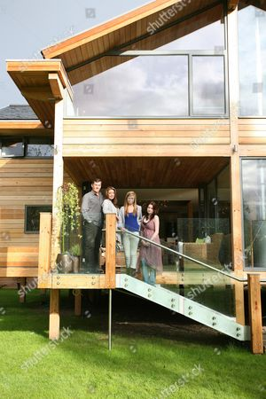 Julia Kendell and her fiance Andrew Hughes-Hallett with daughters Maddy (18) and 15-year-old Sophie (blue top) on the open terrace area of their dream 'Eco' house. Windrush, an eco-friendly house, has been built of Douglas fir timber and glass with raised foundations.