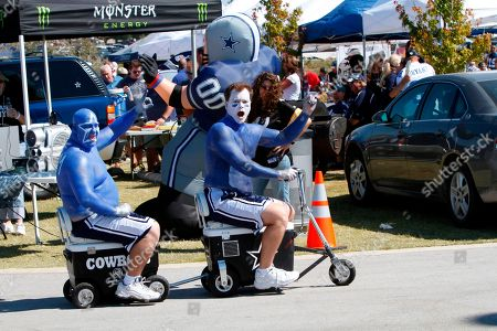 Dallas Cowboys fans Doug Johnson, right, and Chris Hackett ride on motorized ice chest before an NFL football game in Arlington, Texas