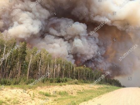Stock Photo of On, provided by the Saskatchewan Ministry of Highways and Infrastructure, smoke billows from a forest fire along highway 969 in southern Saskatchewan, Canada. Saskatchewan Premier Brad Wall says the province's firefighting budget has been depleted, but crews will keep working in the north, where flames and smoke have forced at least 3,000 people from their homes
