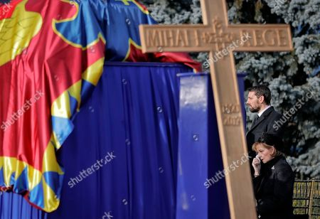 Princess Margaret of Hohenzollern, daughter of former Romanian King Michael I, cries next to his coffin, along with the King's estranged grandson Nicholas Medforth-Mills at Bucharest's Henri Coanda airport, outside Bucharest, Romania, . Former King Michael, who ruled Romania twice and was forced to abdicate by the communists in 1947, died on Dec. 5 in Switzerland at age 96