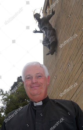 Father David Buckley with the bronze statue of Christ wearing a t-shirt and jeans, on the Our Lady Immaculate and St Philip Neri Catholic church