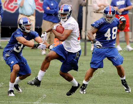 Ramses Barden, Kelvin Smith, Josh Gattis. New York Giants wide receiver Ramses Barden makes a catch between Josh Gattis, left, and Kelvin Smith, right, at rookie football mincamp in East Rutherford, N.J