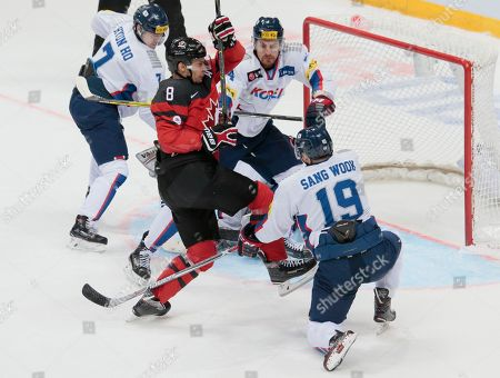Canada's Wojtek Wolski, centre, tries to score against Korea's defenders during the Channel One Cup ice hockey match between Canada and Korea in Moscow, Russia, on