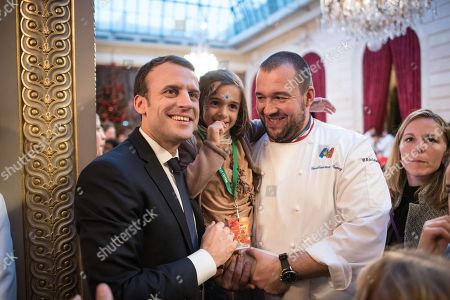 French President Emmanuel Macron and his wife Brigitte (with French chef Guillaume Gomez) attend the Elysee Christmas for children, on December 13, 2017, at the Elysee Presidential palace in Paris.