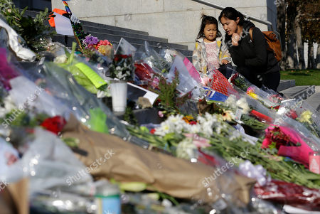 Diana Wang talks with her daughter Leah after leaving flowers for Mayor Ed Lee on the steps of City Hall in San Francisco, . Lee died Tuesday at 65 after collapsing while grocery shopping