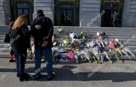 A woman and man pause to look at a memorial for Mayor Ed Lee on the steps of City Hall in San Francisco, . Lee died Tuesday at 65 after collapsing while grocery shopping