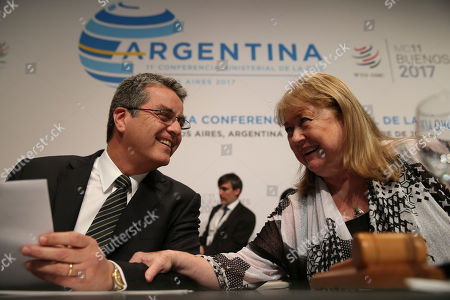 Stock Image of World Trade Organization Director General Roberto Azevedo, left, and WTO Ministerial Conference President Susana Malcorra talk during the closing ceremony of the WTO Ministerial Conference in Buenos Aires, Argentina