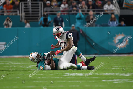 Julius Thomas #89 of Miami is tackled by Patrick Chung #23 of New England during the NFL football game between the Miami Dolphins and New England Patriots at Hard Rock Stadium in Miami Gardens FL. The Dolphins defeated the Patriots 27-20