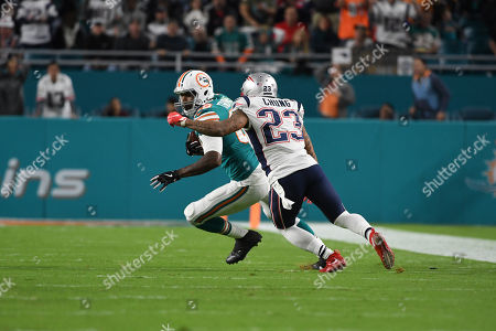 Stock Image of Julius Thomas #89 of Miami is chased and tackled by Patrick Chung #23 of New England after recovering his own fumble during the NFL football game between the Miami Dolphins and New England Patriots at Hard Rock Stadium in Miami Gardens FL. The Dolphins defeated the Patriots 27-20