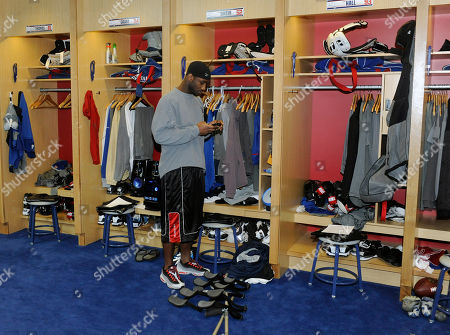 New York Giants' Clint Sintim checks his messages as the Giants clean out their lockers after their NFL football season ended in East Rutherford, N.J