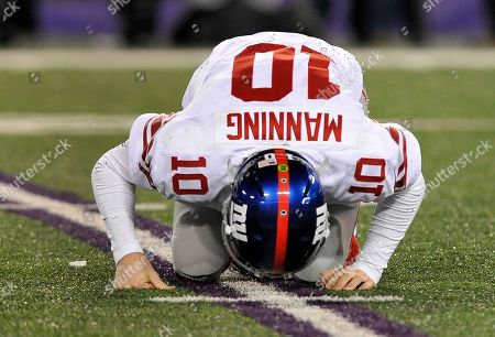 New York Giants quarterback Eli Manning gets up after being knocked over by Baltimore Ravens inside linebacker Brendon Ayanbadejo in the second half of an NFL football game in Baltimore