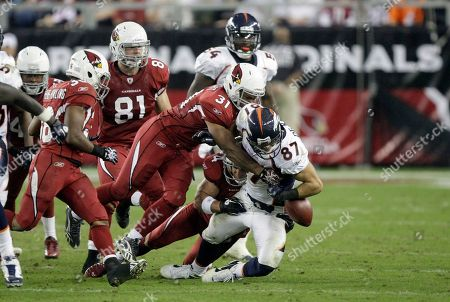 Eric Decker, Jason Wright, Jay Feeley. Denver Broncos' Eric Decker (87) is tackled by Arizona Cardinals' Jason Wright (31) and Jay Feeley (4) during an NFL football game, in Glendale, Ariz