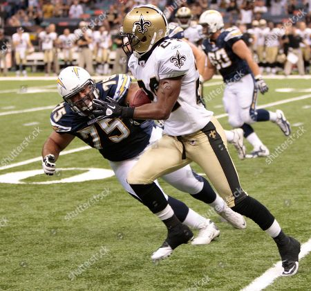 Stock Photo of Leigh Torrence, Corey Clark. New Orleans Saints cornerback Leigh Torrence (24) runs past San Diego Chargers offensive tackle Corey Clark (75) with an interception in an NFL preseason football game in the Louisiana Superdome in New Orleans, . The Saints defeated the Chargers 36-21