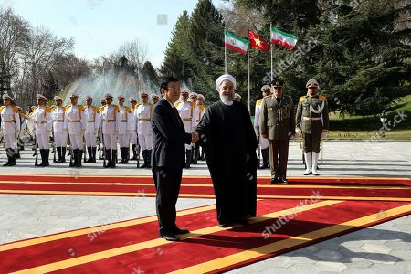 Hassan Rouhani, Truong Tan Sang. In this photo released by official website of the office of the Iranian Presidency, President Hassan Rouhani, right, shakes hands with Vietnam's President Truong Tan Sang, for photographs prior to their meeting in Tehran, Iran