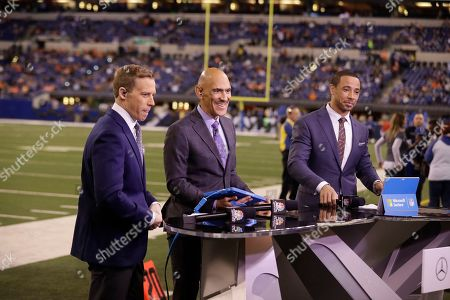 Liam McHugh, from left, Tony Dungy and Rodney Harrison talk on set before an NFL football game between the Indianapolis Colts and Denver Broncos in Indianapolis