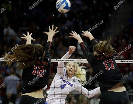 Florida middle blocker Darrielle King (2) hits the ball over Stanford middle blocker Audriana Fitzmorris (12) and opposite Merete Lutz (17) during an NCAA Division I volleyball semifinal game, in Kansas City, Mo