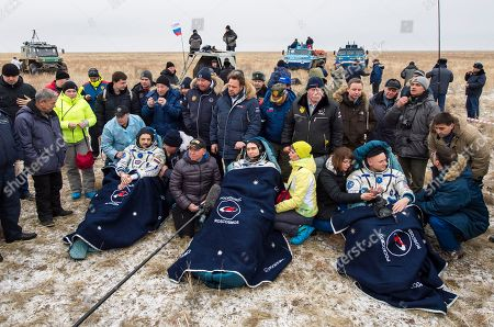 Russian cosmonauts Mikhail Kornienko, left, Sergey Volkov, center, and U.S. astronaut Scott Kelly rest in chairs outside the Soyuz TMA-18M space capsule after they landed in a remote area outside the town of Dzhezkazgan, Kazakhstan, on . Kelly and Kornienko are completing an International Space Station record year-long mission to collect valuable data on the effect of long duration weightlessness on the human body that will be used to formulate a human mission to Mars. Volkov is returning after six months on the station