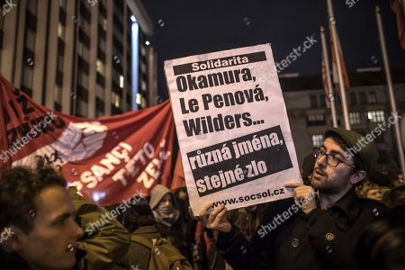 A demonstrator holds a banner 'Okamura, Le Pen, Wilders...different names, the same evil' as he protests against a conference of the European right-wing party ENF (Europe Nations and Freedom) in Prague, Czech Republic, 15 December 2017. The leaders of European parties Marine Le Pen, Geert Wilders, Georg Mayer, Tomio Okamura, Michal Marusik, Marcus Pretzell etc. will attend to ENF conference in Prague on 16 December 2017.