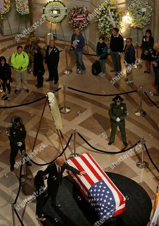 Steve Kawa, former chief of staff to San Francisco Mayor Ed Lee, places his hand on the casket containing the body of Lee lying in repose in the San Francisco City Hall rotunda,, in San Francisco. Lee died early Tuesday, Dec. 12, after collapsing at a grocery store, leaving the city reeling from shock and dealing with the logistics of selecting a new leader