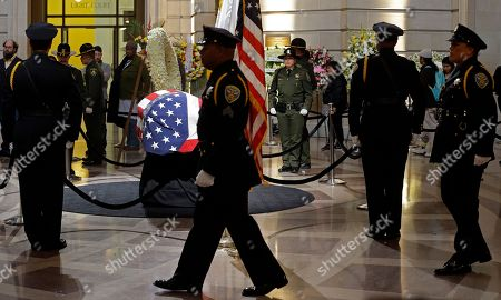 Law enforcement officers change guard around the casket containing the body of Mayor Ed Lee lying in repose in the San Francisco City Hall rotunda,, in San Francisco. Lee died early Tuesday after collapsing at a grocery store, leaving the city reeling from shock and dealing with the logistics of selecting a new leader