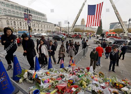 Mourners walk past flowers left for Mayor Ed Lee as they enter San Francisco City Hall rotunda to view Lee lying in repose, in San Francisco. Lee died early Tuesday, Dec. 12, after collapsing at a grocery store, leaving the city reeling from shock and dealing with the logistics of selecting a new leader
