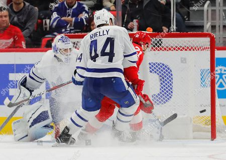 Detroit Red Wings left wing Tomas Tatar (21) scores on Toronto Maple Leafs goalie Curtis McElhinney (35) as Morgan Rielly (44) looks on in the third period of an NHL hockey game, in Detroit