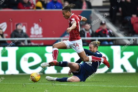 Bobby Reid (14) of Bristol City leaps over Matthew Mills (5) of Nottingham Forset who is attempting to tackle him during the EFL Sky Bet Championship match between Bristol City and Nottingham Forest at Ashton Gate, Bristol