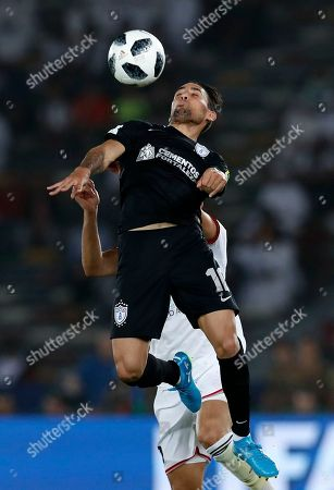 Pachuca's Jonathan Urretaviscaya jumps for the ball with Al Jazira's Musallem Fayez, background, during the Club World Cup third place soccer match between Al Jazira and CF Pachuca at Zayed Sports City stadium in Abu Dhabi, United Arab Emirates