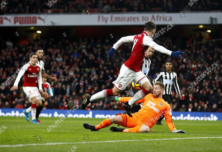 Arsenal's Mesut Ozil shot is stopped by Newcastle United's 'keeper Rob Elliot during the Premier League match between Arsenal and Newcastle United at the Emirates Stadium, London