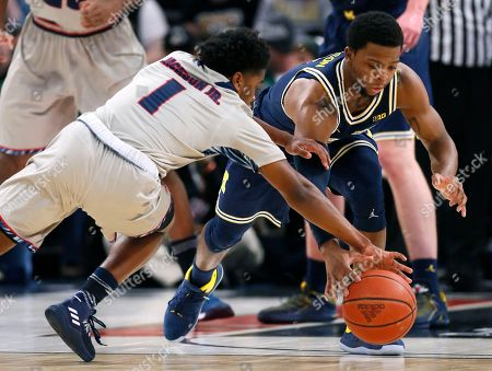 Stock Picture of Jermaine Jackson Jr., Zavier Simpson. Detroit's Jermaine Jackson Jr. (1) and Michigan's Zavier Simpson chase a loose ball during the first half of an NCAA college basketball game, in Detroit