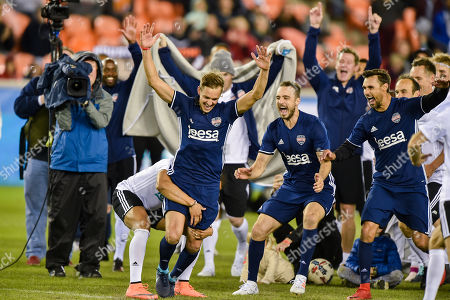 Stuart Holden is surrounded as he celebrates making a penalty kick during the Kick In for Houston celebrity charity soccer match at BBVA Compass Stadium in Houston, TX