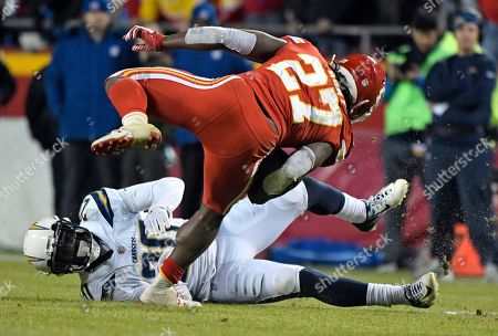 Kareem Hunt, Desmond King. Kansas City Chiefs running back Kareem Hunt (27) tries to keep his balance against Los Angeles Chargers defensive back Desmond King (20) during the second half of an NFL football game in Kansas City, Mo