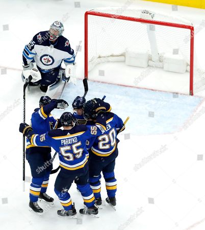 Teammates surround St. Louis Blues' Vladimir Tarasenko (91), of Russia, after he scored past Winnipeg Jets goalie Steve Mason, top, during the first period of an NHL hockey game, in St. Louis