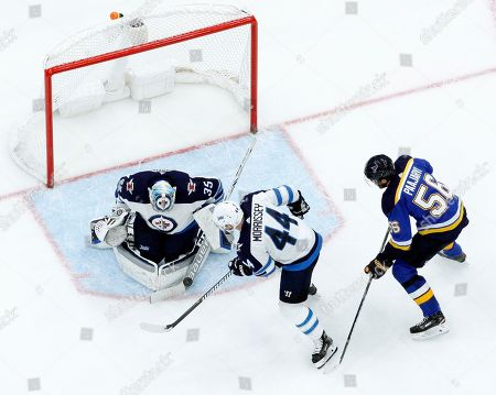 Winnipeg Jets goalie Steve Mason (35) blocks a puck as teammate Josh Morrissey and St. Louis Blues' Magnus Paajarvi (56), of Sweden, watch during the second period of an NHL hockey game, in St. Louis