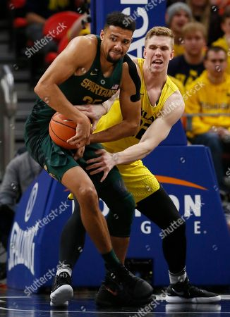 Stock Photo of Kenny Goins, Tom Cotter. Michigan State forward Kenny Goins (25) takes the ball away from Oakland forward Tom Cotter (32) during the second half of an NCAA college basketball game, in Detroit. Michigan State defeated Oakland 86-73